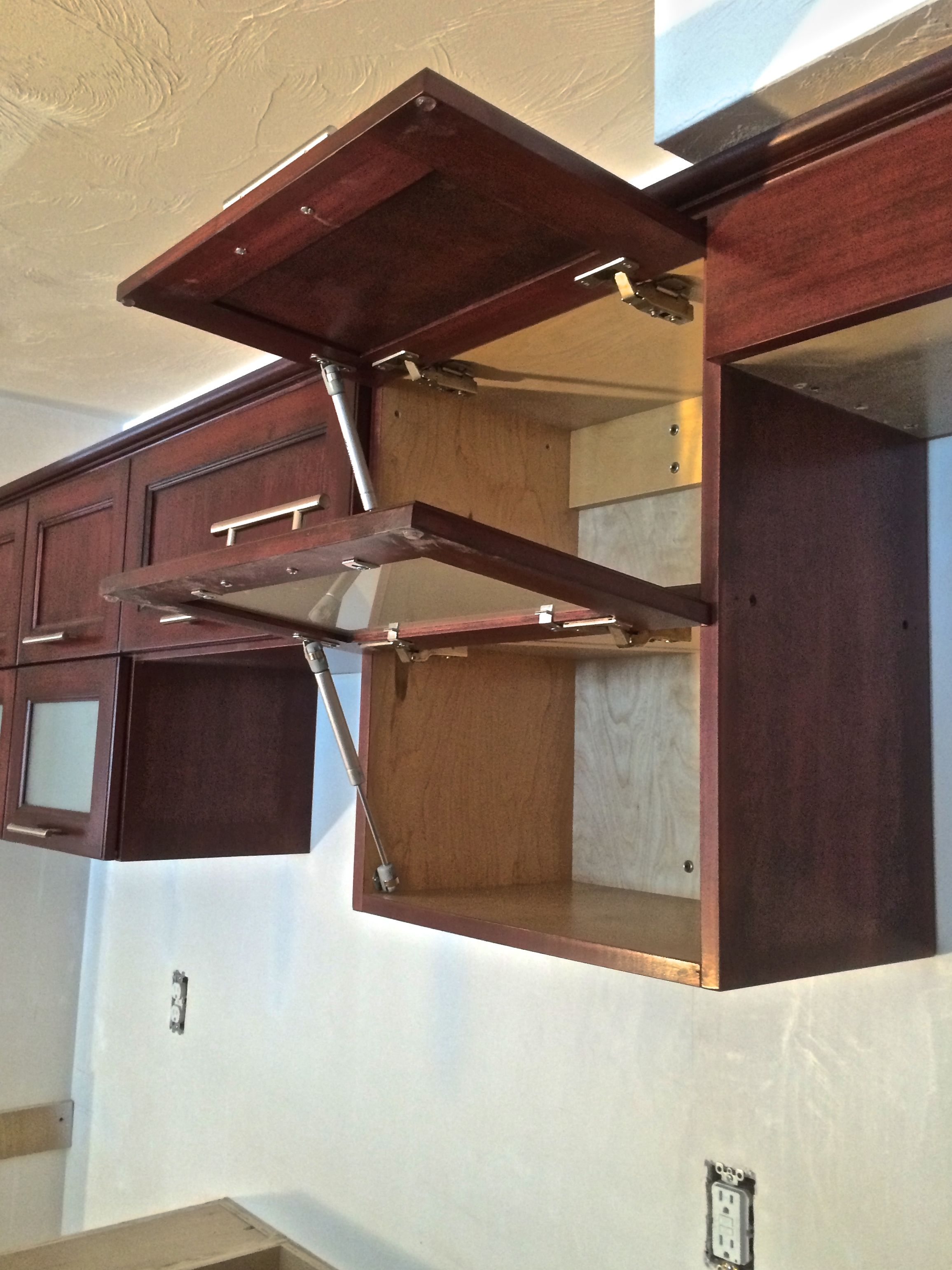 Basement In Law Kitchen Flip Up Doors On Maple Cabinets With A Rich Mahogany Stain Frosted Glass Com Quality Custom Cabinetry Custom Cabinetry Maple Cabinets