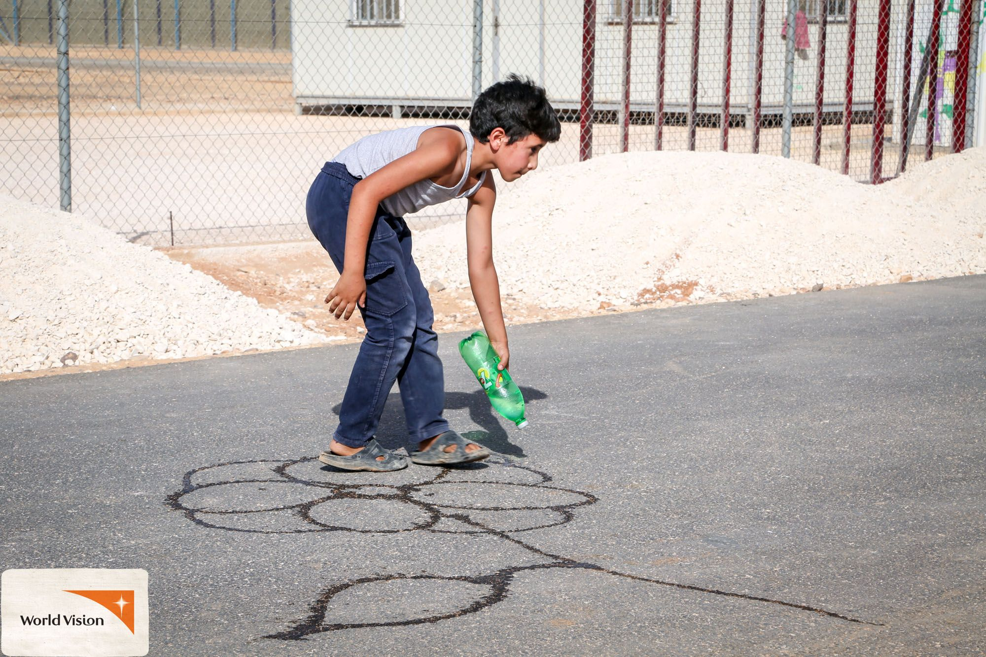 Abdullah, a 12-year-old #Syrian #refugee, loves drawing in the streets using #water! Photo by Elias Abu Ata, #WorldVision