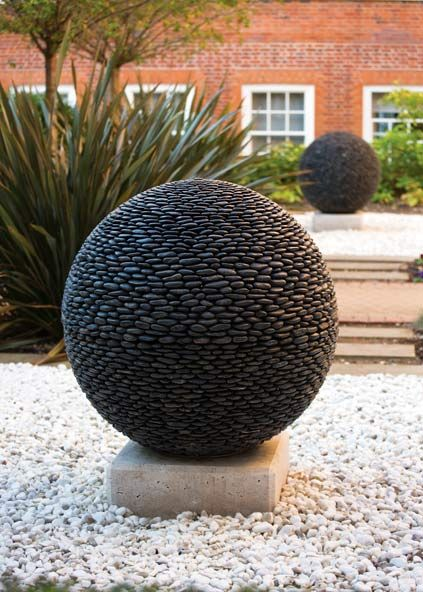 Perfectly Symmetrical Spheres Made From Hundreds of River Stones is part of Garden spheres - These geometric, natureinspired spheres made from hundreds of smooth river stones look like they belong on the grounds of a palace  The stunning garden