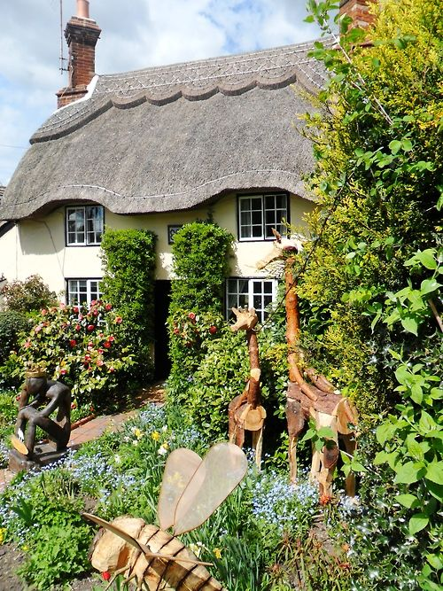 Thatched Cottage with wooden garden ornaments, Market Bosworth, Leicestershire, England