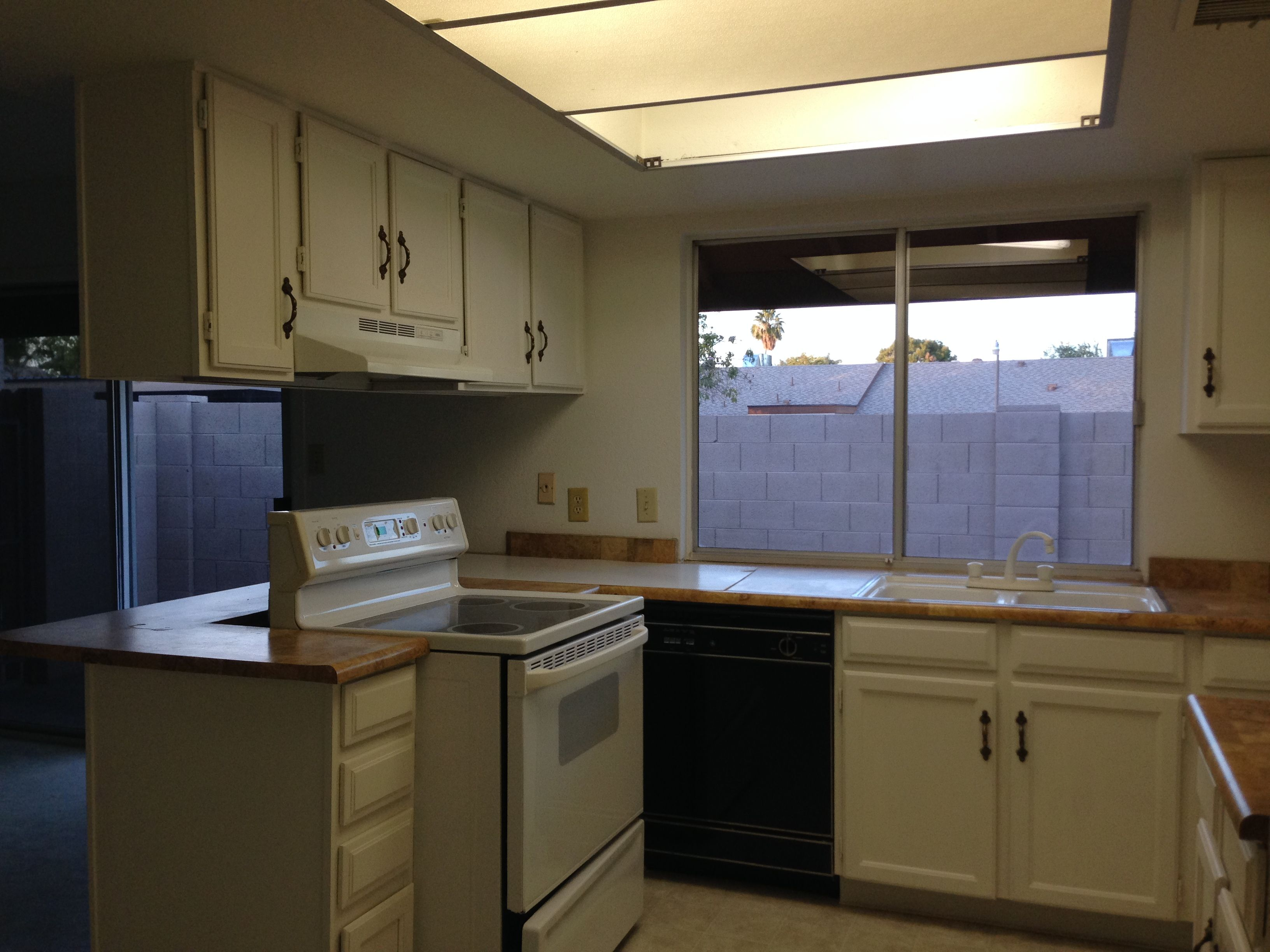 Kitchen before 7 foot ceiling with 30 1970s cabinets 4 x 6 fluorescent light w x 48h oversized window