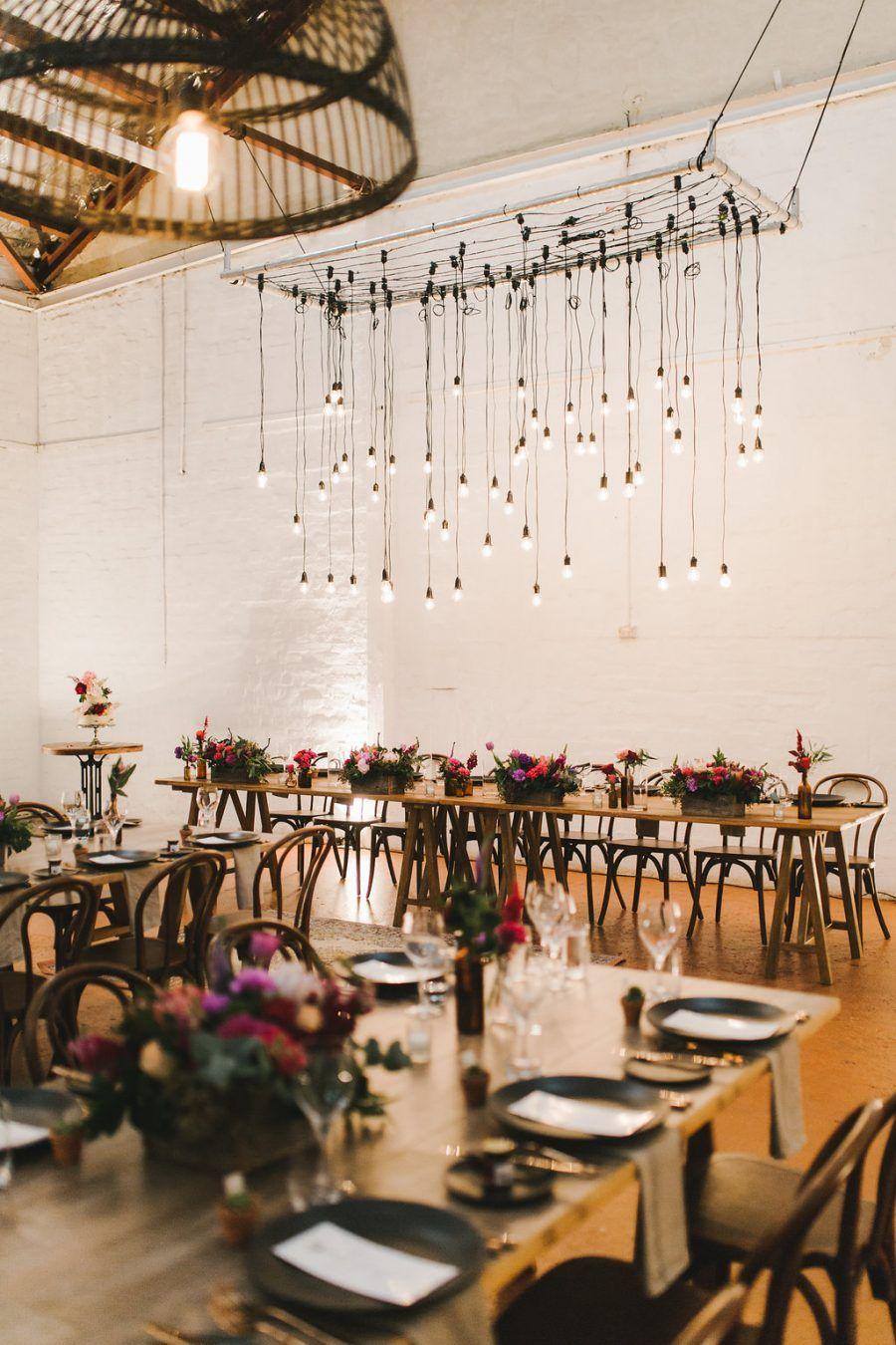 Farm wedding decor ideas  industrial warehouse wedding with suspended lighting installation