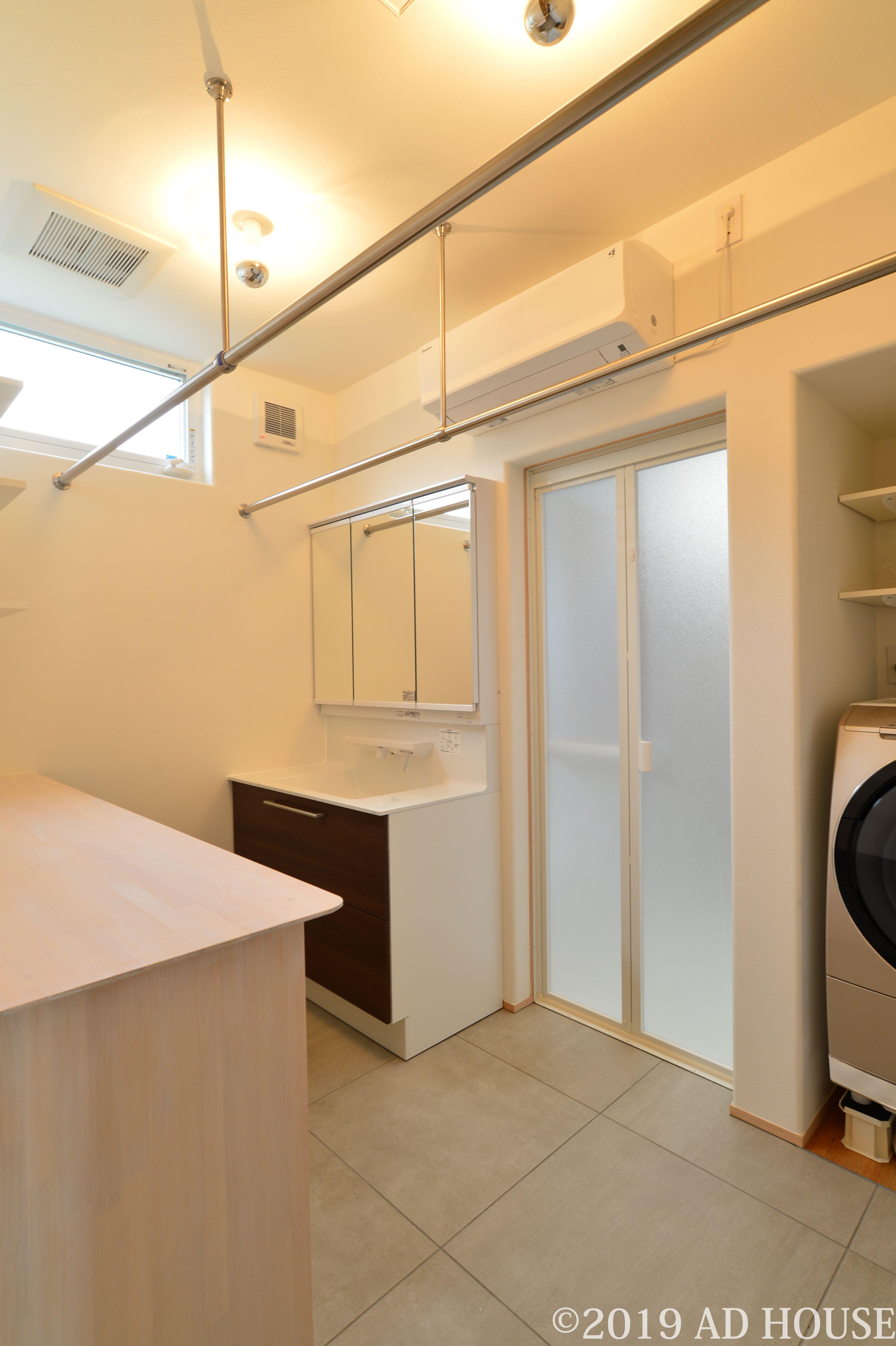 室内干しを想定した洗濯脱衣室 3畳ほど 浴室側の床仕上げをタイルにして掃除をしやすく作業カウンターを設けていて アイロンがけもできるように カウンター下には手持ち