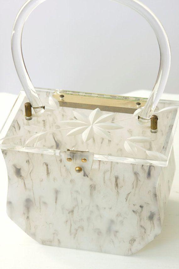"""Wonderful 1950s lucite box purse in a black and white pearly, marbled pattern. Lid is clear lucite with a carved flower and leaf design. Curved clear lucite handle. Hinged snap closure. A beautiful and collectible purse! <> MEASUREMENTS <>  Lid length: 6 1/2"""" Lid width: 4"""" Box length at widest point: 6"""" Box base: 3 1/2"""" x 3 3/4"""" Height: 4 3/4"""" to top of box From top of purse to top of handle: 5 1/2"""" Handle: 6"""" wide  <> MATERIALS, LABELS AND DETAILS <>  Made of lucite plastic. There are no…"""