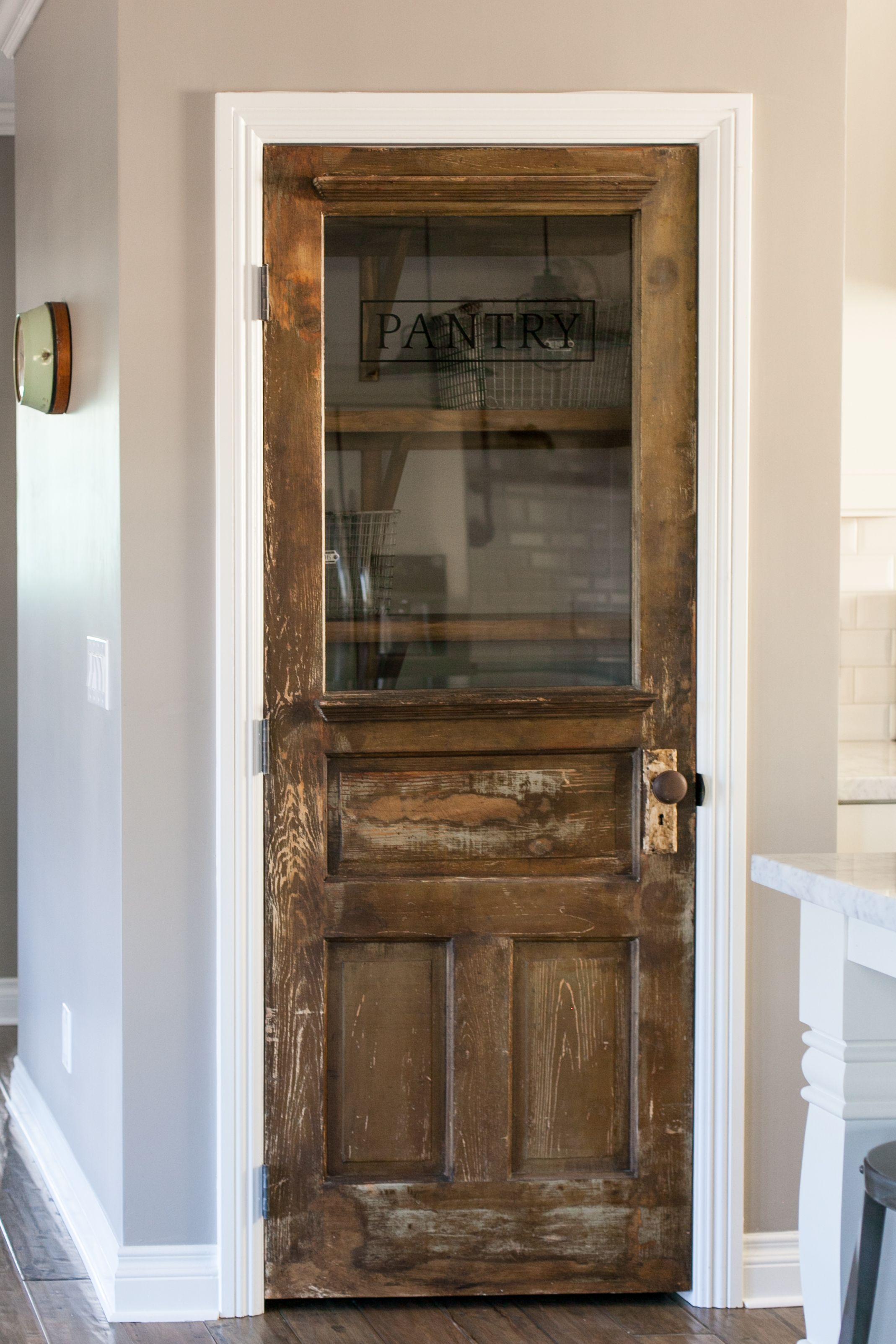 Vintage farmhouse door repurposed as a pantry door by