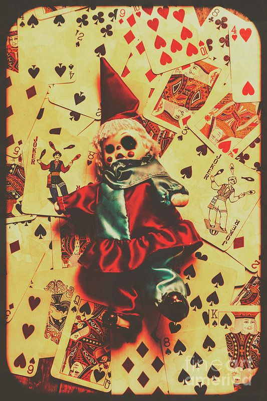Spooky evil clown toy doll on scattered casino playing cards ...