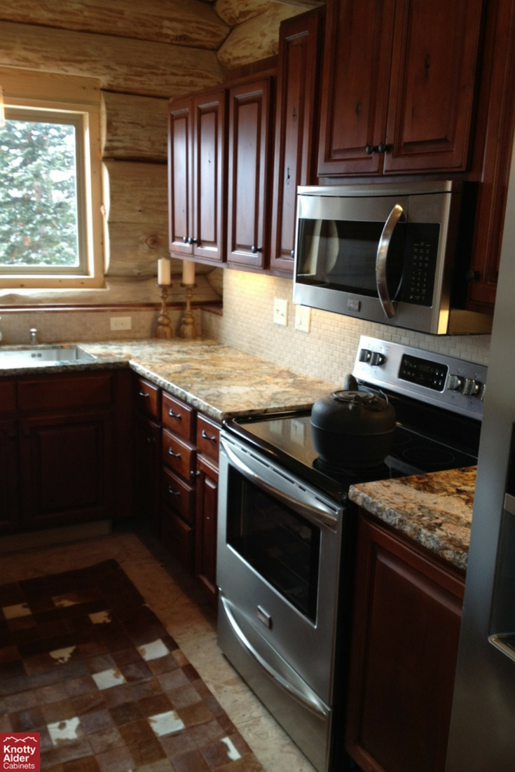 Our dark glazed kitchen cabinets against a tan back splash kitchen