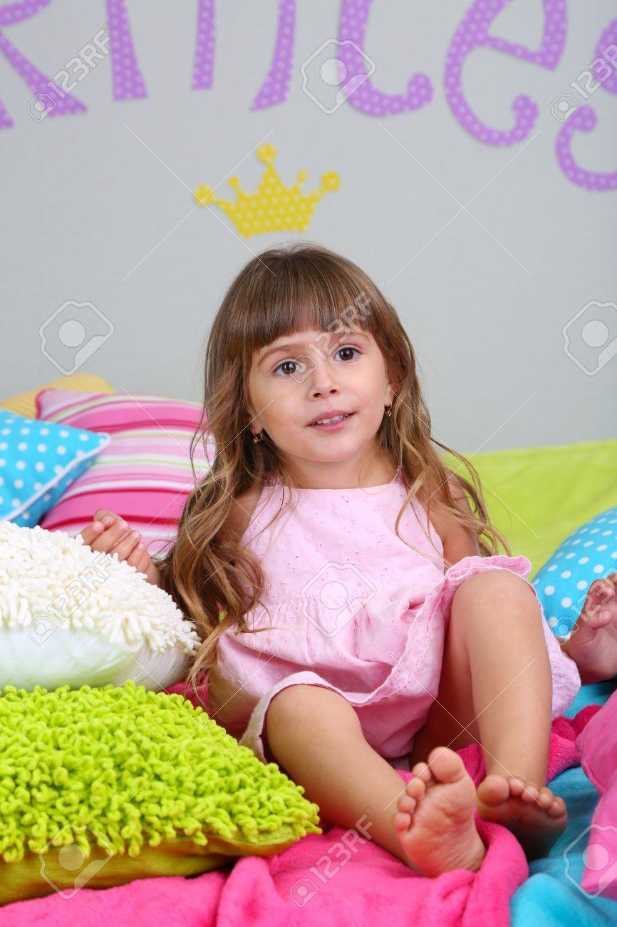Kleines Mädchen sitzt auf dem Bett im Zimmer auf grau Wand