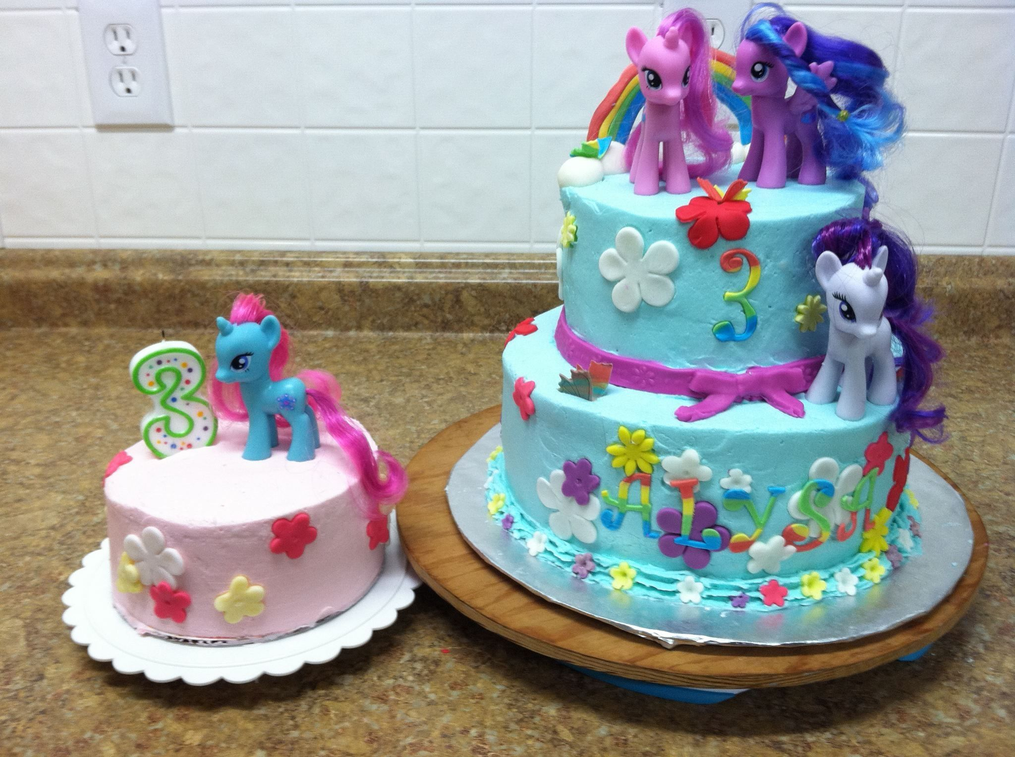 My Little Pony - This cake was for my niece's 3rd birthday party.  It is a WASC but colored rainbow with buttercream frosting.  LOTS of problems with this cake.  I couldn't get the buttercream smooth, then when I tried to do the Viva towel method (never tried it before) it only made it worse.  Then when I go to take it to my sister's house my fist went right into the side of it!  So I had to make a bunch more fondant flowers to cover.  She was happy though!