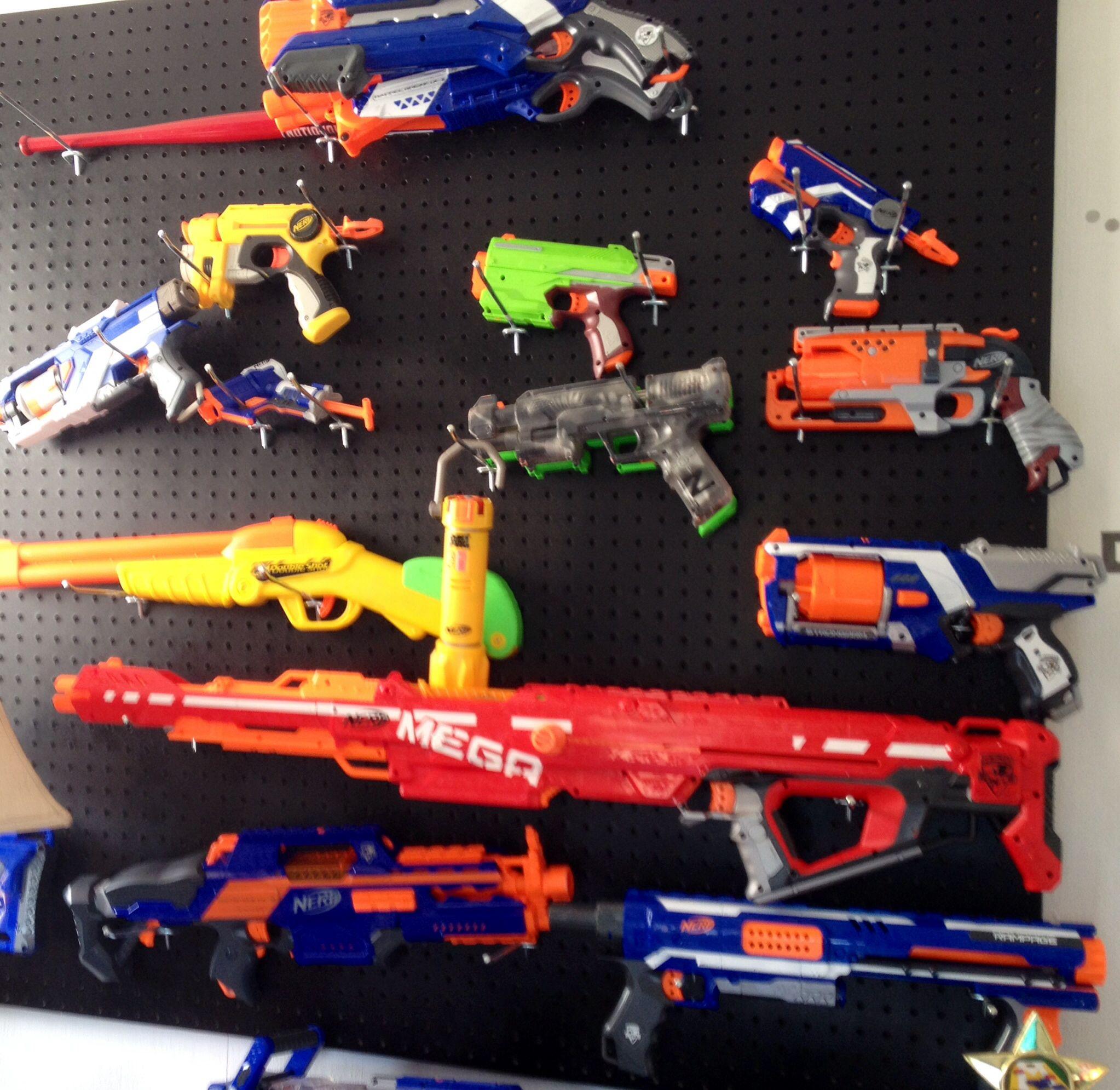 Nerf gun arsenal. Peg board spray painted black. Hang the guns on the pegs