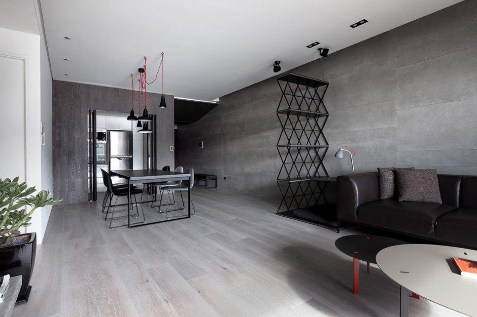 Strefę dzienną wizualnie scala ściana wyłożona w całości wielkoformatowymi betonowymi płytami oraz jednorodna podłoga w kolorze bielonego drewna. Projekt: Circle Huang i Gina Chou. Fot. Hey! Cheese.