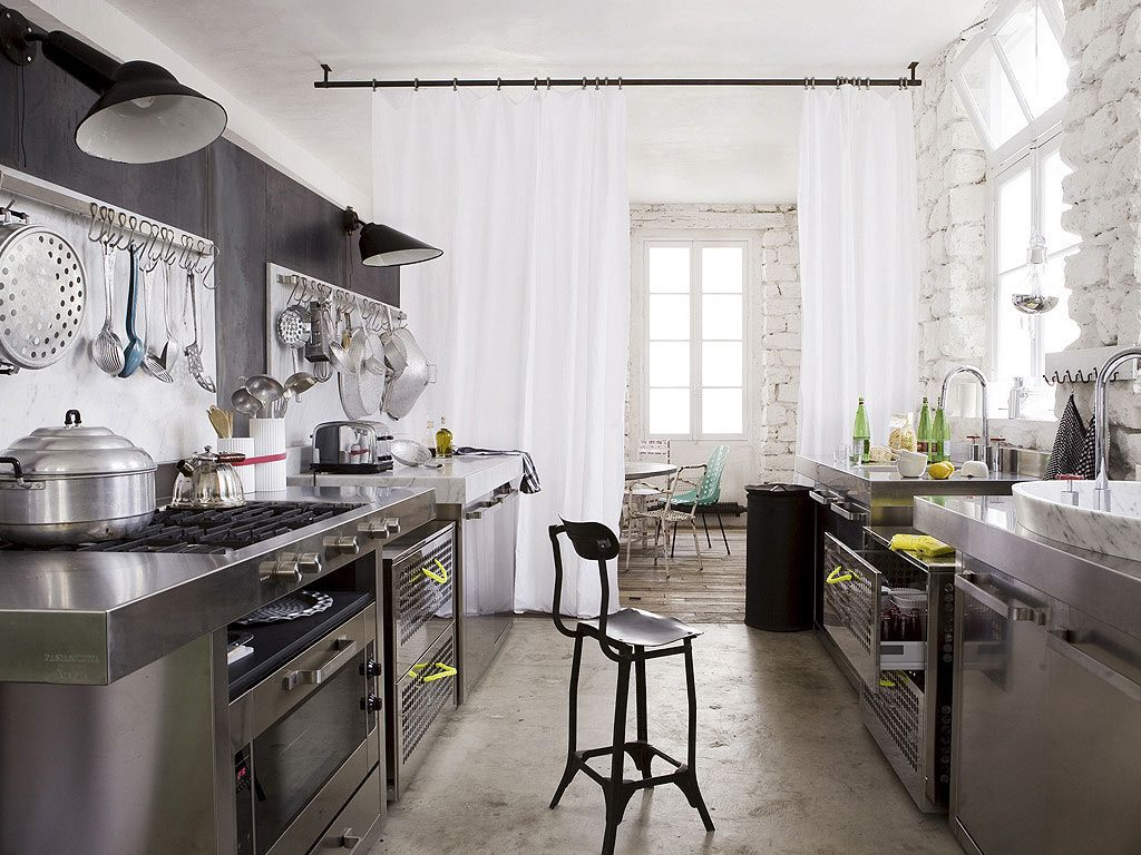 stainless steel kitchen + whitewashed stone walls + white curtains ...