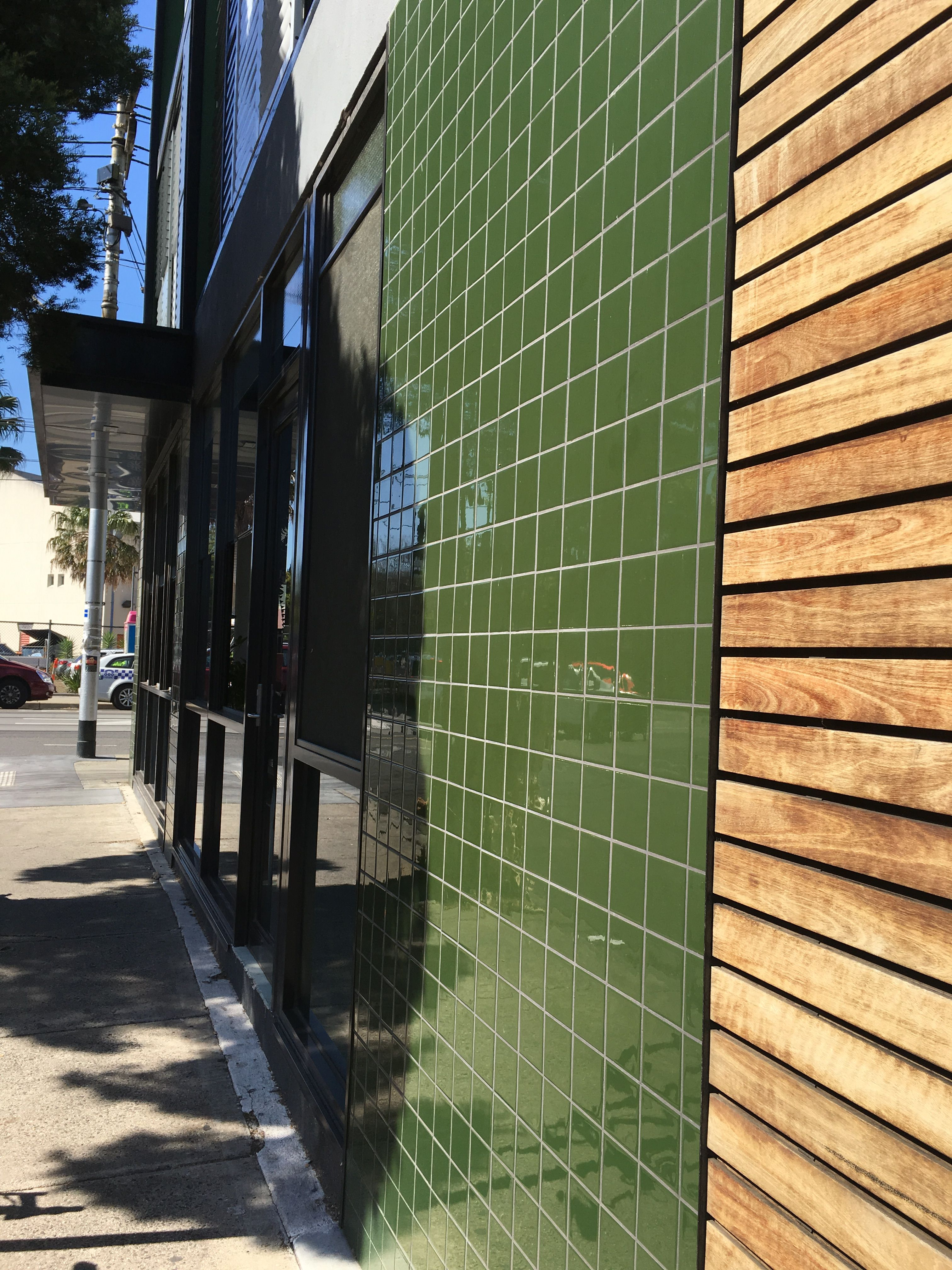 PHOTO 5: The green tiles outside this Melbourne coffee shop contrast organically with the wood slats and add to the modern decor of the exterior space.