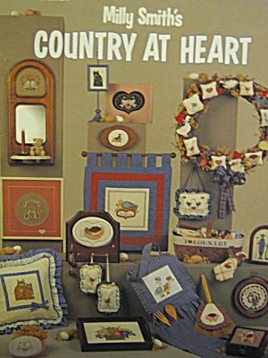 Leisure Arts Cross Stitch Milly Smith's Country At Heart #404.Twenty designs and a country alphabet shown in 42 projects.