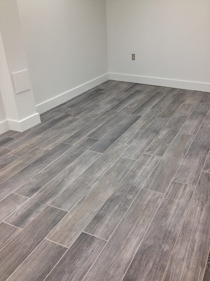 Gray Floors Are All The Rage This Season Grey Wood Tile Gray Wood Tile Flooring House Flooring