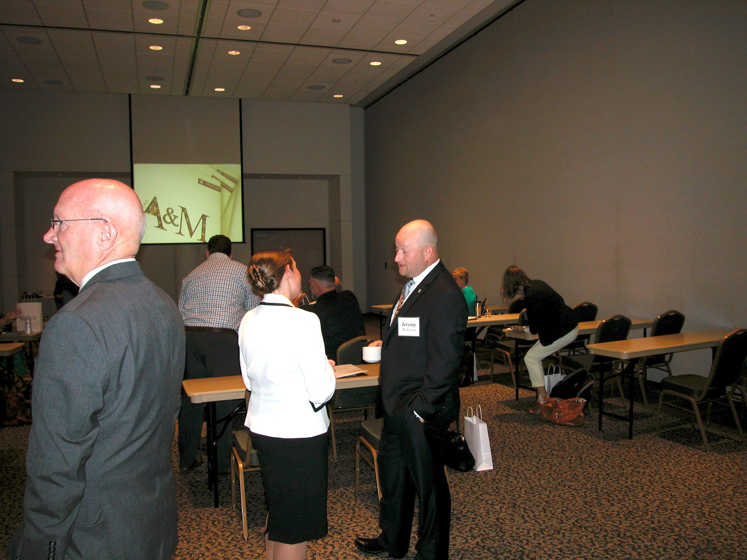 Executive students chat with faculty and staff before the EMPSA Program Introduction