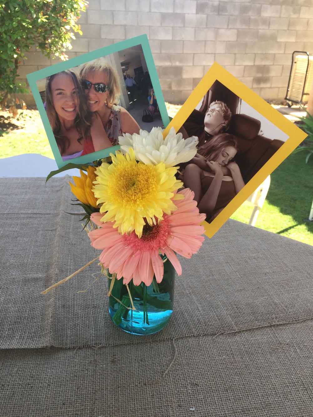 Colorful centerpieces on burlap tablecloths. Then and now pictures, in blue mason jars with raffia bow, gerber daisies with sunflowers.