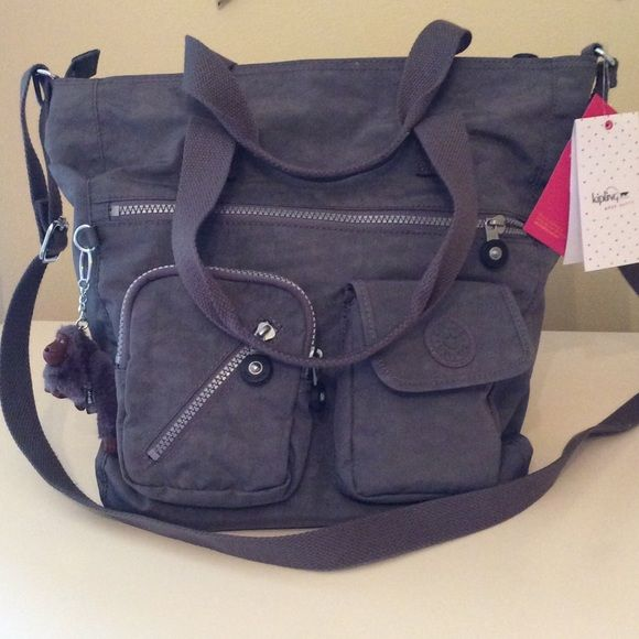 Kipling Gray Tote This bag is a great grab & go tote. So much storage! Will hold all your essentials for work or play such as laptop/iPad. Wear on shoulder or Crossbody. Kipling Bags Crossbody Bags