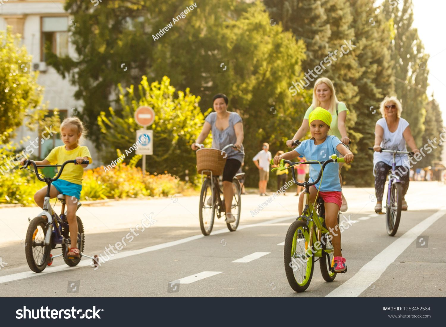 Theme family active sports outdoor recreation A group of people is a big family of 6 people standing posing on mountain bikes in a city park on a road on a sunny day in a...