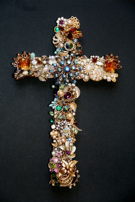 The base of this cross is a wood with a metallic gold finish. There are many rhinestones and /or gemstones in a varity of colors include blue,