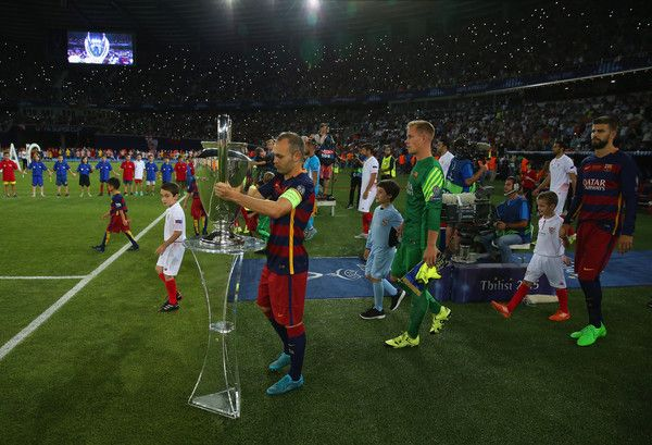 Andres Iniesta Of Barcelona Places The Champions League Trophy Pitchside Prior To UEFA Super Cup Between And Sevilla FC At Dinamo Arena On