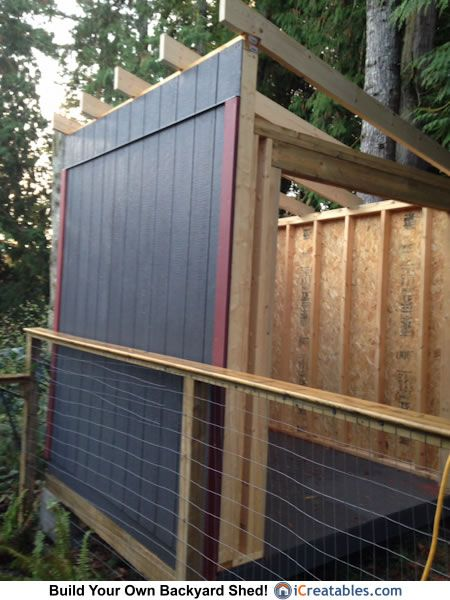 Lean to shed built up against fence. Wall is painted ...