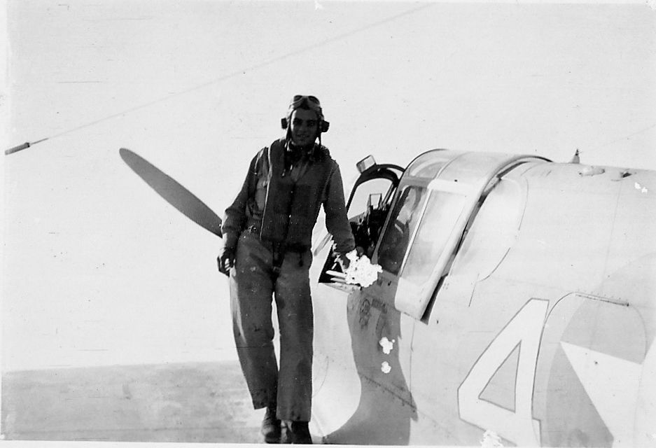 Lt. Guy O. Denton, 57th Fighter Group, 65th Fighter Squadron, standing on the wing of his P-40 Warhawk in North Africa, Fall, 1942,