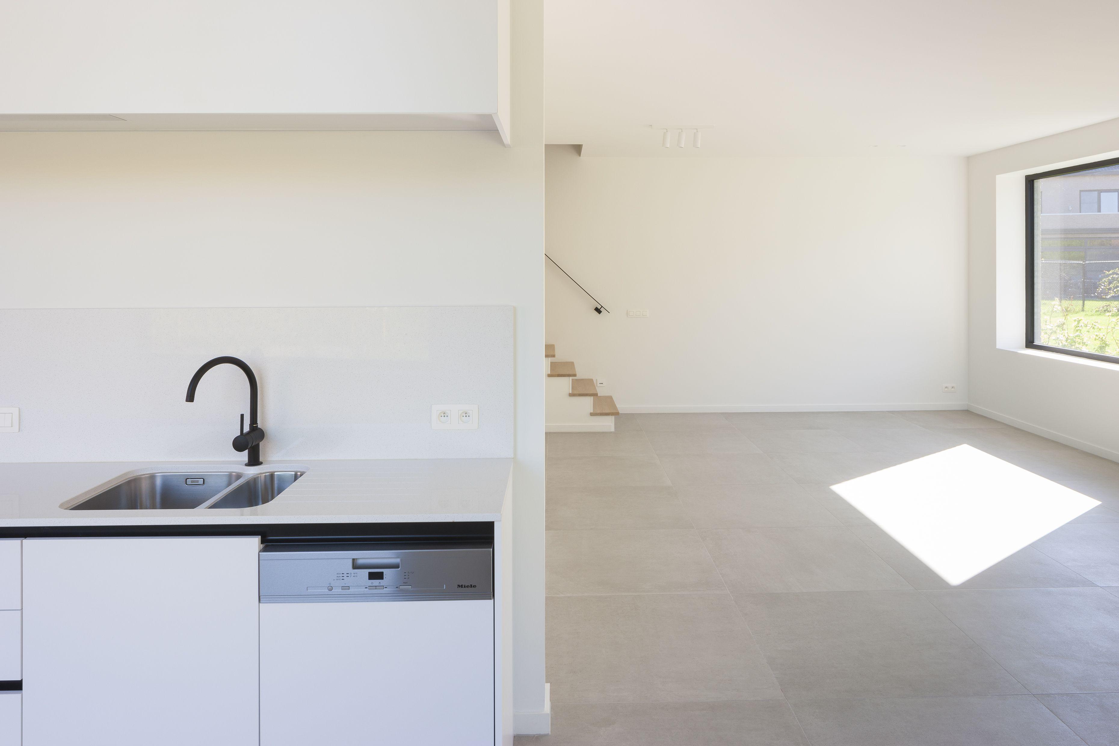 Moderne witte keuken met zwarte accenten en zwarte grohe kraan