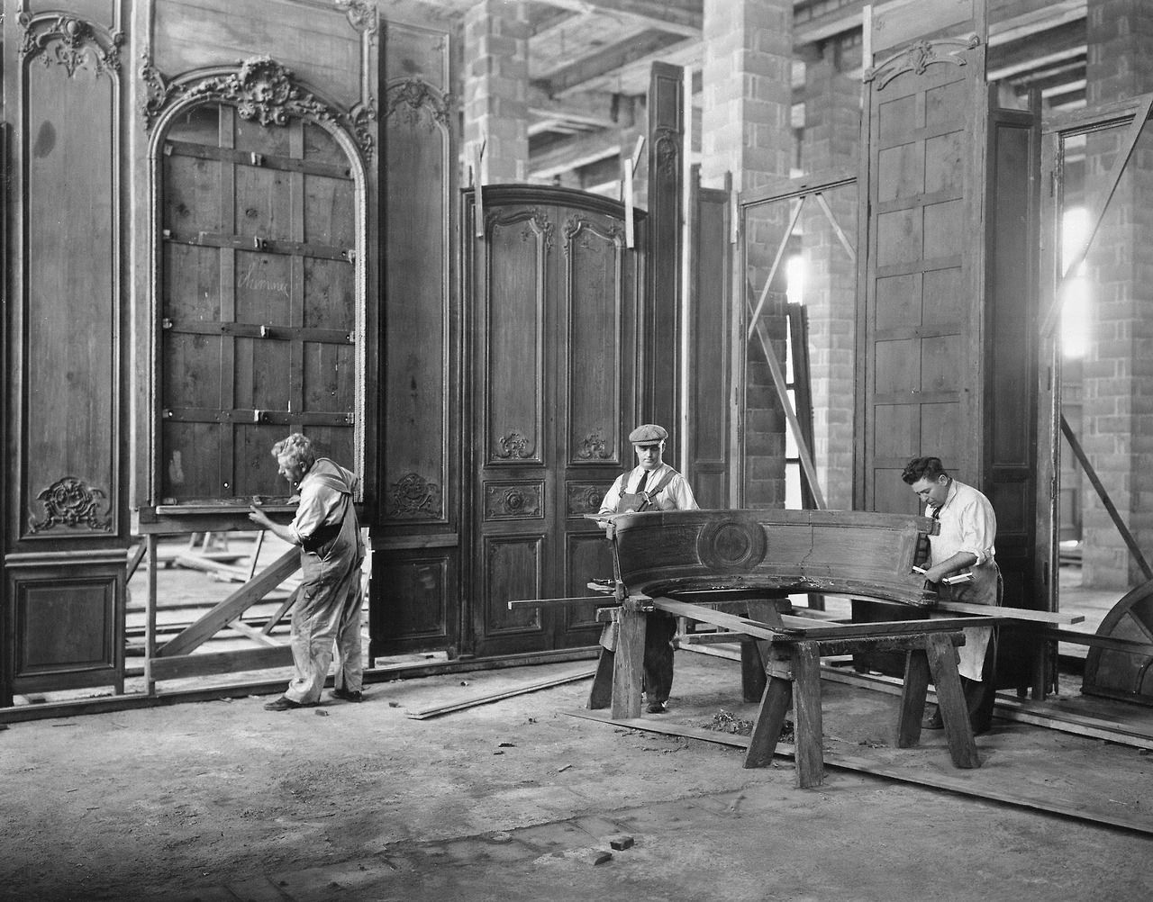 Workers install the ornate carved paneling of the Grand