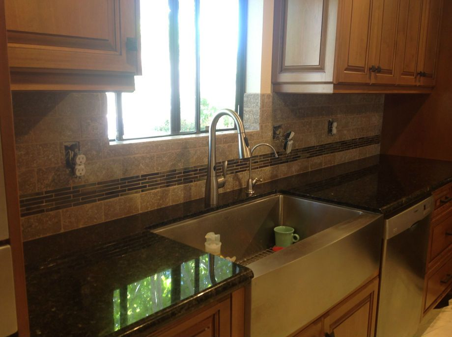 Absolute Black Granite Countertops With A Travertine Tile Backsplash And  Linear Mosaic Liner. Apron Front
