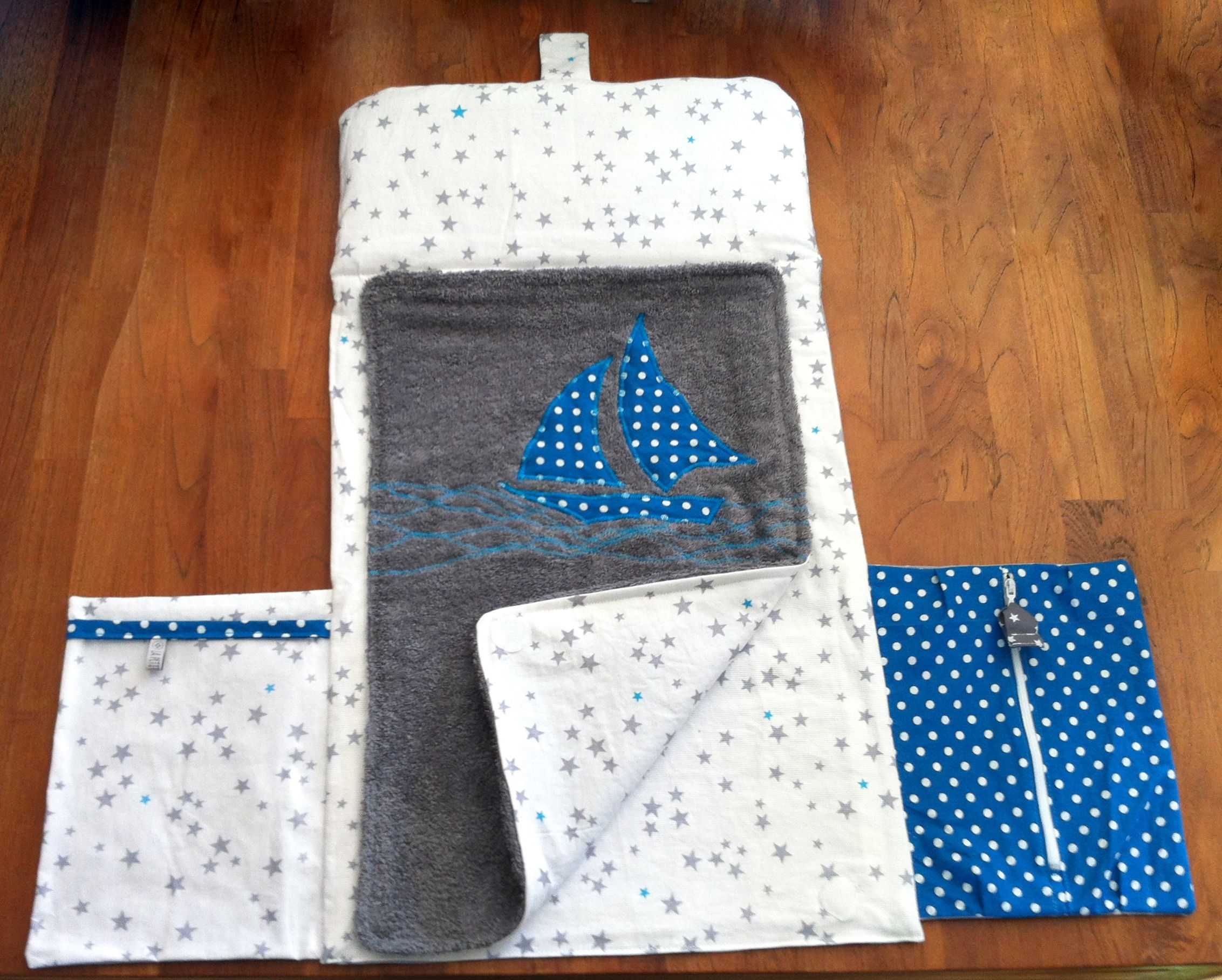Pochette à langer , comprenant un tapis en coton et coton enduit avec 2 poches pour couches et lingettes et un tapis à langer détachable en coton et tissu éponge .   https://www.facebook.com/LaPetiteCouturieuse