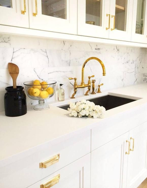 glam kitchen features white glass front upper cabinets adorned with gold pulls over white lower on kitchen remodel gold hardware id=89042