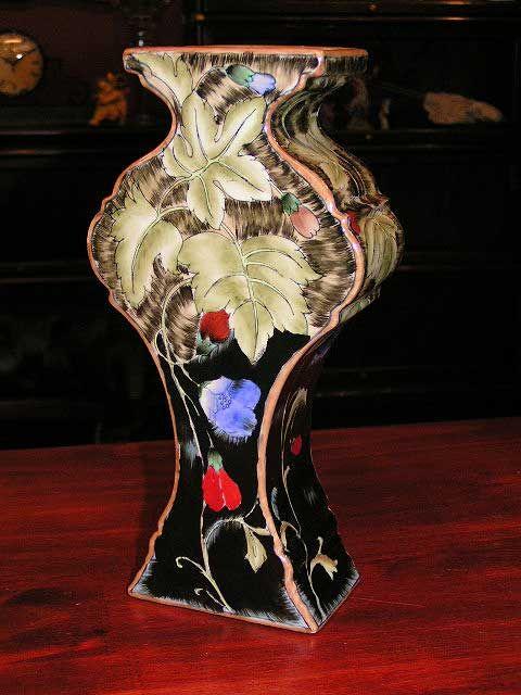 Prachtige vaas met een afbeelding van een blad met bloemen. De afbeelding is in relief op de vaas gebakken. Een sieraad voor in uw huis. Materiaal: Keramiek/ Plateel Afmetingen: Hoogte: 25 cm Breedte: 13 cm Diepte: 7 cm