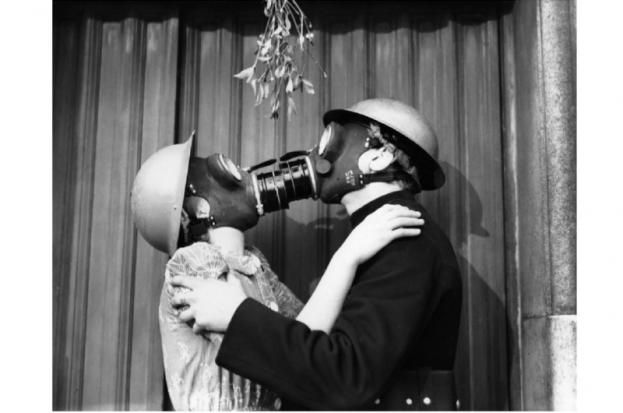 A couple kissing under the mistletoe wearing gas masks, 1940. (Photo by Fox Photos/Getty Images)