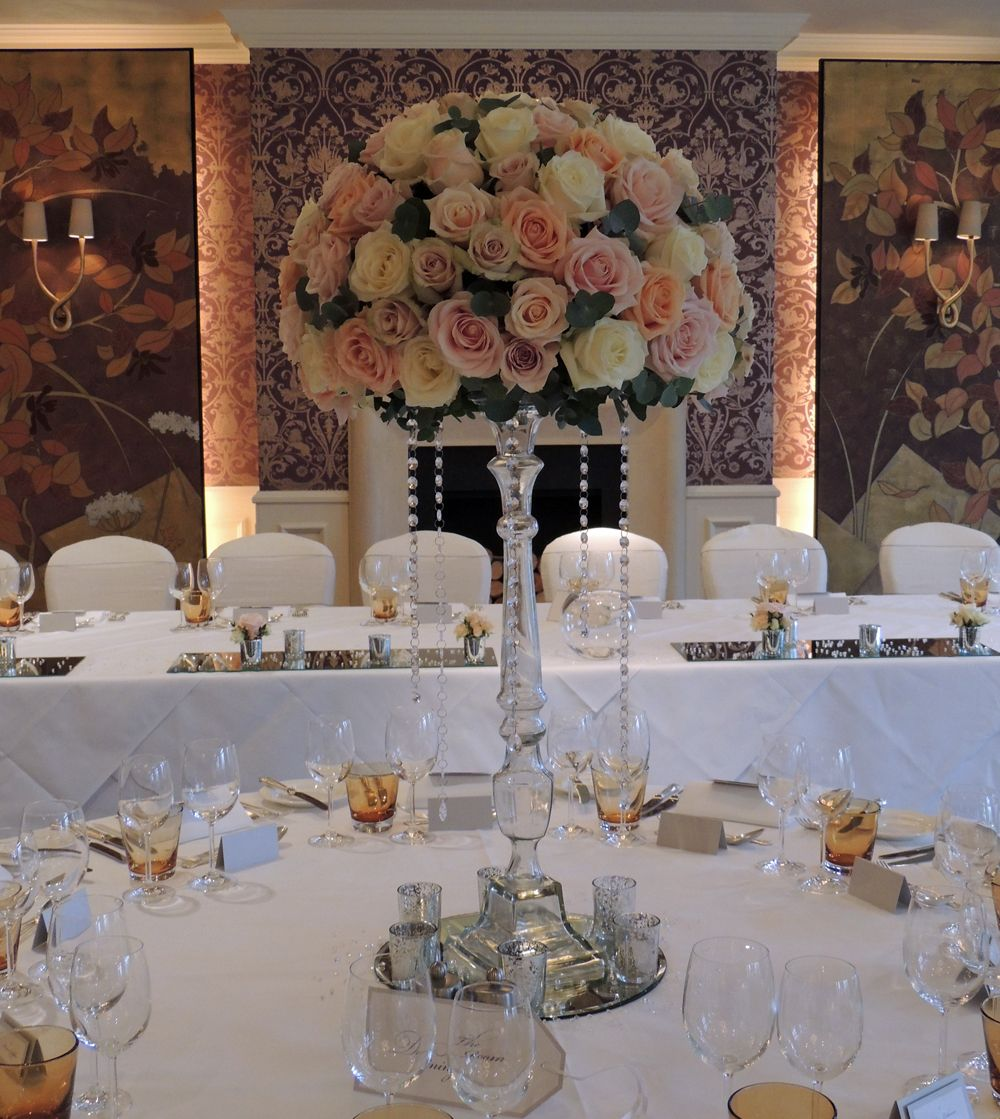 Very large rose dome in pale pink, peach, blush and ivory standing on a glass candlestick with hanging crystals