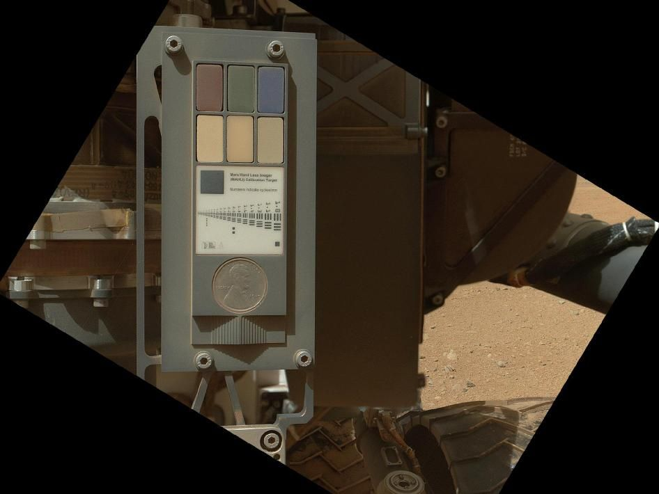 Calibration Target for Curiosity's Arm Camera. This view of the calibration target for the Mars Hand Lens Imager (MAHLI) aboard NASA's Mars rover Curiosity combines two images taken by that camera during the 34th Martian day, or sol, of Curiosity's work on Mars (Sept. 9, 2012). Part of Curiosity's left-front and center wheels and a patch of Martian ground are also visible.