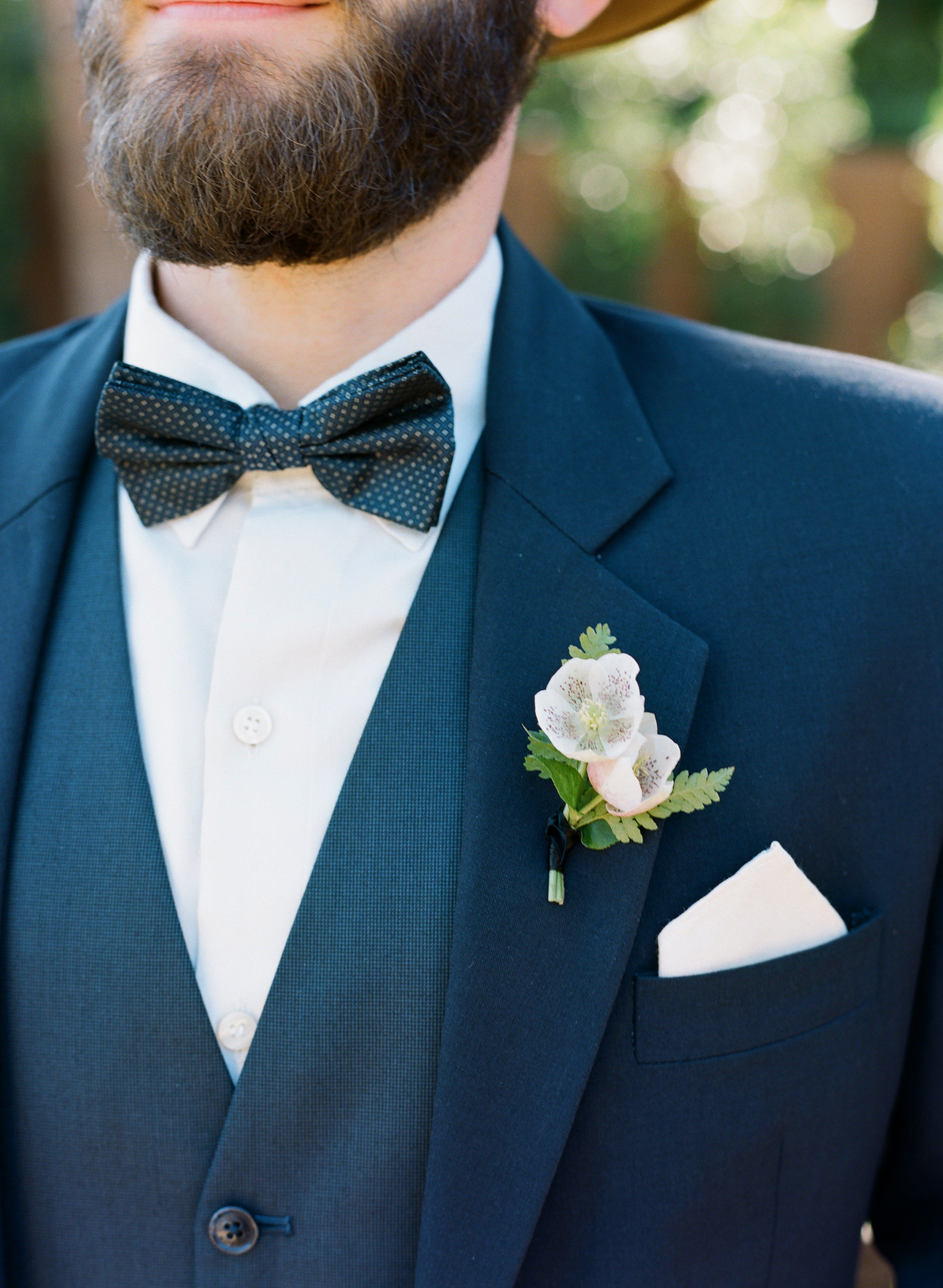 99ef4453e24a ... groom is wearing a custom navy blue suit. He styled the suit with a  dotted bow tie, blush pink and green floral boutonniere and a simple pocket  square.