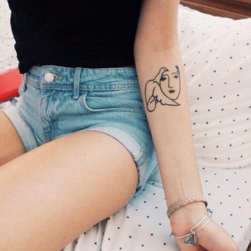 Picasso line drawing arm tattoo