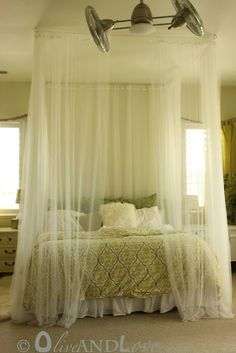 DIY Ceiling mounted bed canopy consisting of eyebolts, turn buckles and wire thread through sheer curtains.