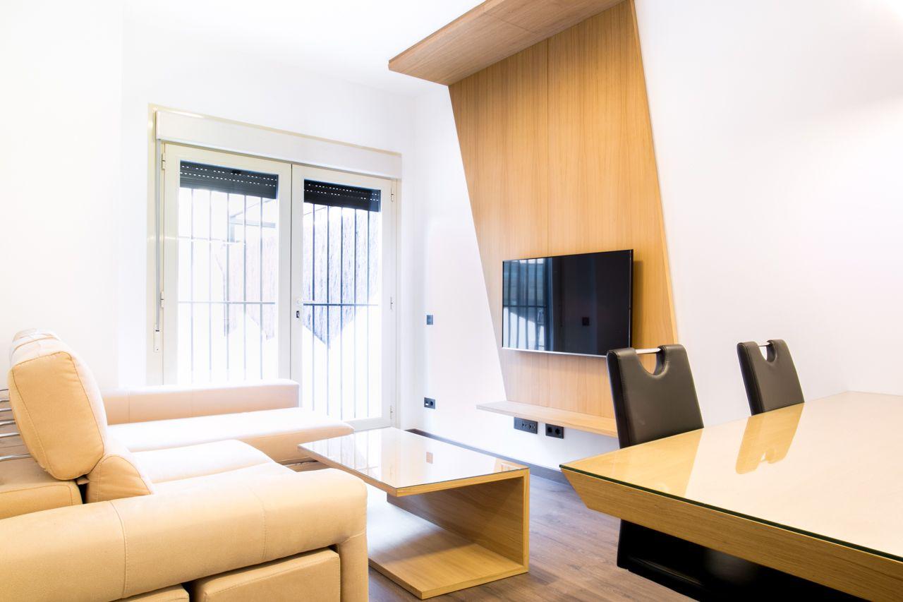 Salón de diseño moderno, mueble de tv realizado a medida en madera natural junto a la mesa de centro.