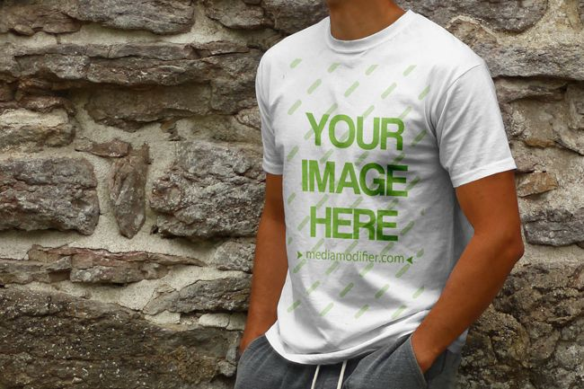 Download Online Mockup Generator Template With A Young White Male Standing On A Stone Wall Background A Realistic T Shirt Mo Shirt Mockup Clothing Mockup Tshirt Mockup