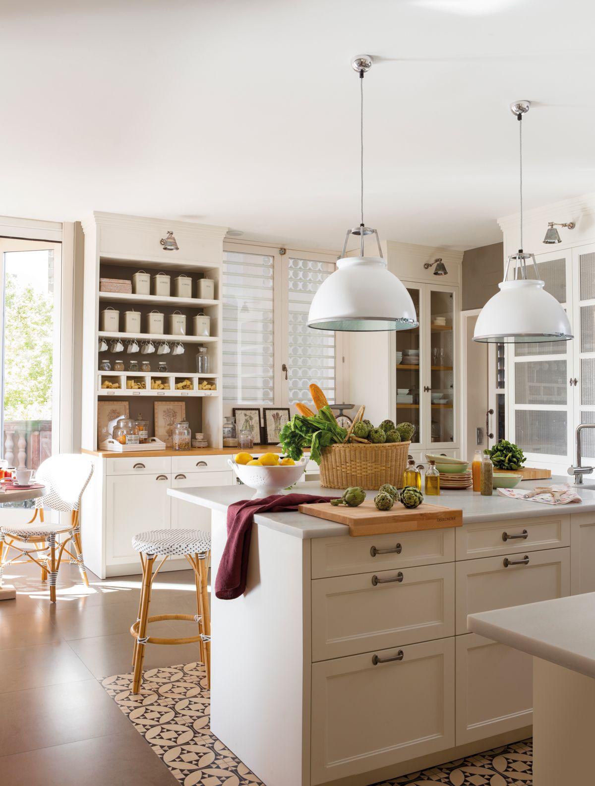 Cocina blanca con isla con zona de fuegos y campana, y pavimento de ...