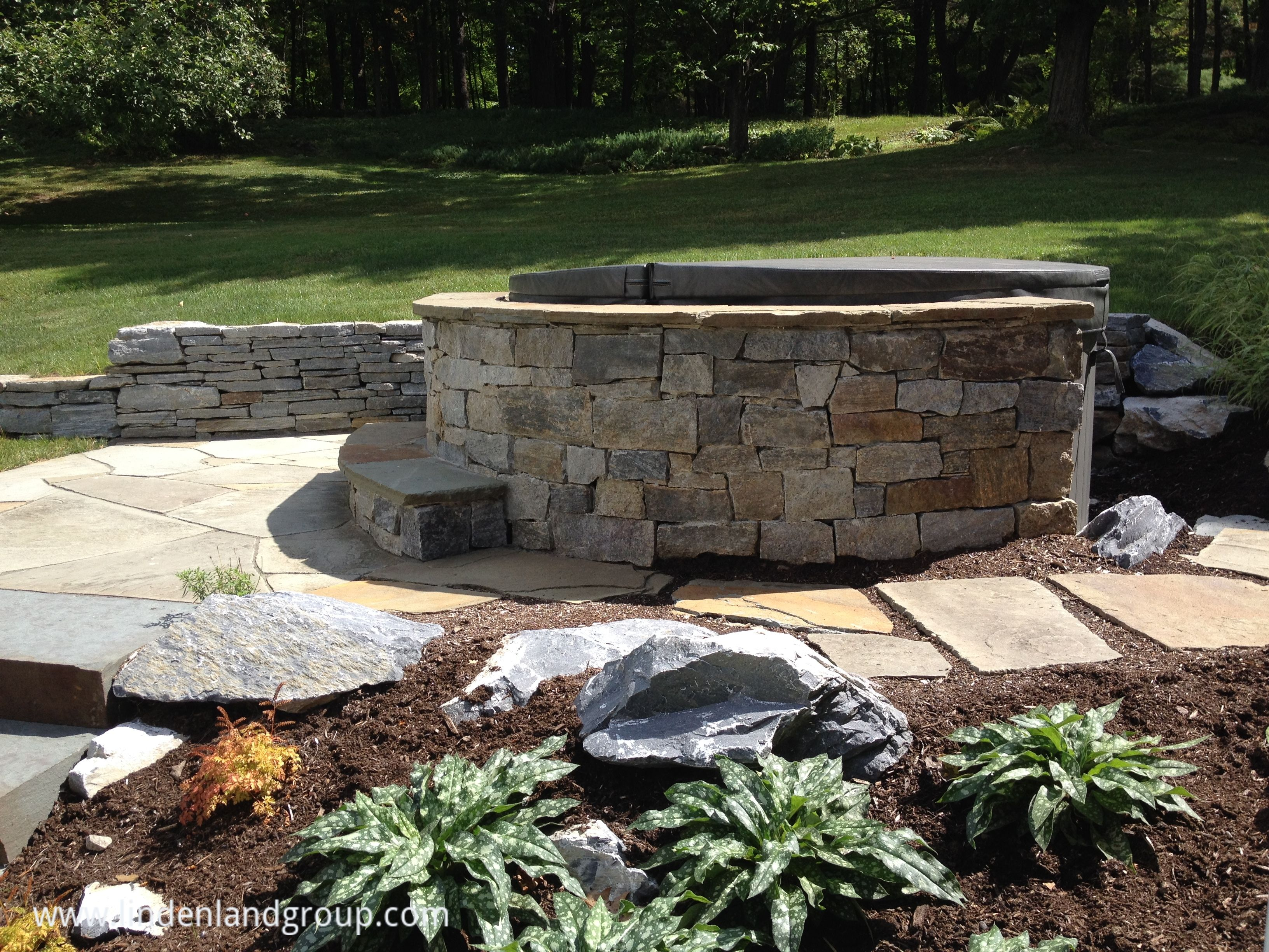 The natural stone steps of a stairway garden feature climb a small - Check Out The Natural Stone Spa Surround For This Middlebury Vt Client A Popular Landscape