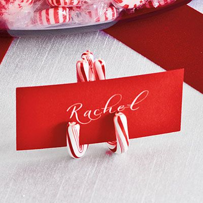 DIY Candy Cane Place Card Holder   Secure three mini candy canes with double-sided tape to make easels for place cards.