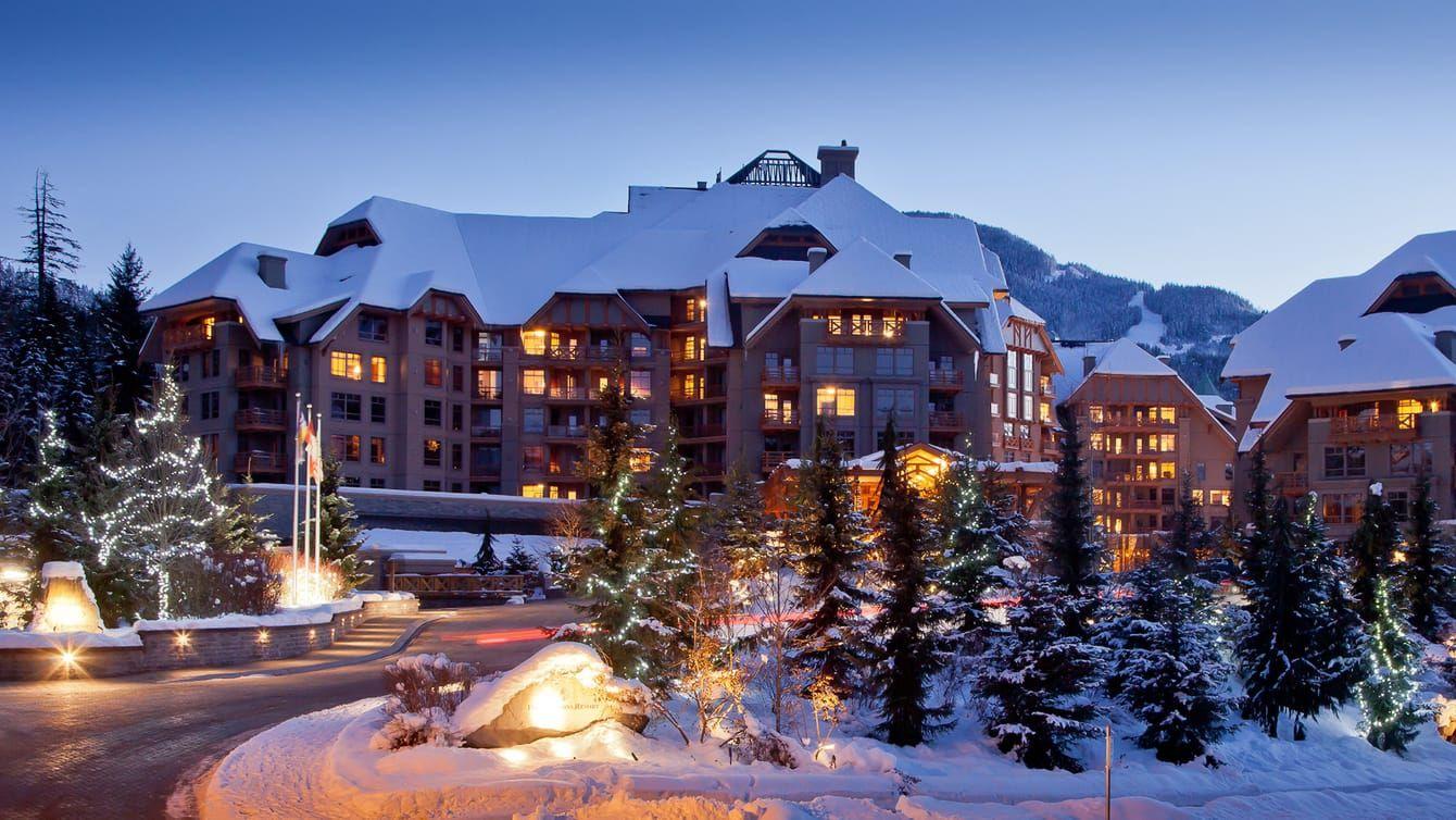 snowy four seasons hotel whistler ski lodge at dusk with illuminated