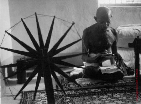 "Gandhi and the spinning wheel by Margaret Bourke-White in 1947.  Gandhi said, ""Machinery in the past has made us dependent on England, and the only way we can rid ourselves of the dependence is to boycott all goods made by machinery. This is why we have made it the patriotic duty of every Indian to spin his own cotton and weave his own cloth."""
