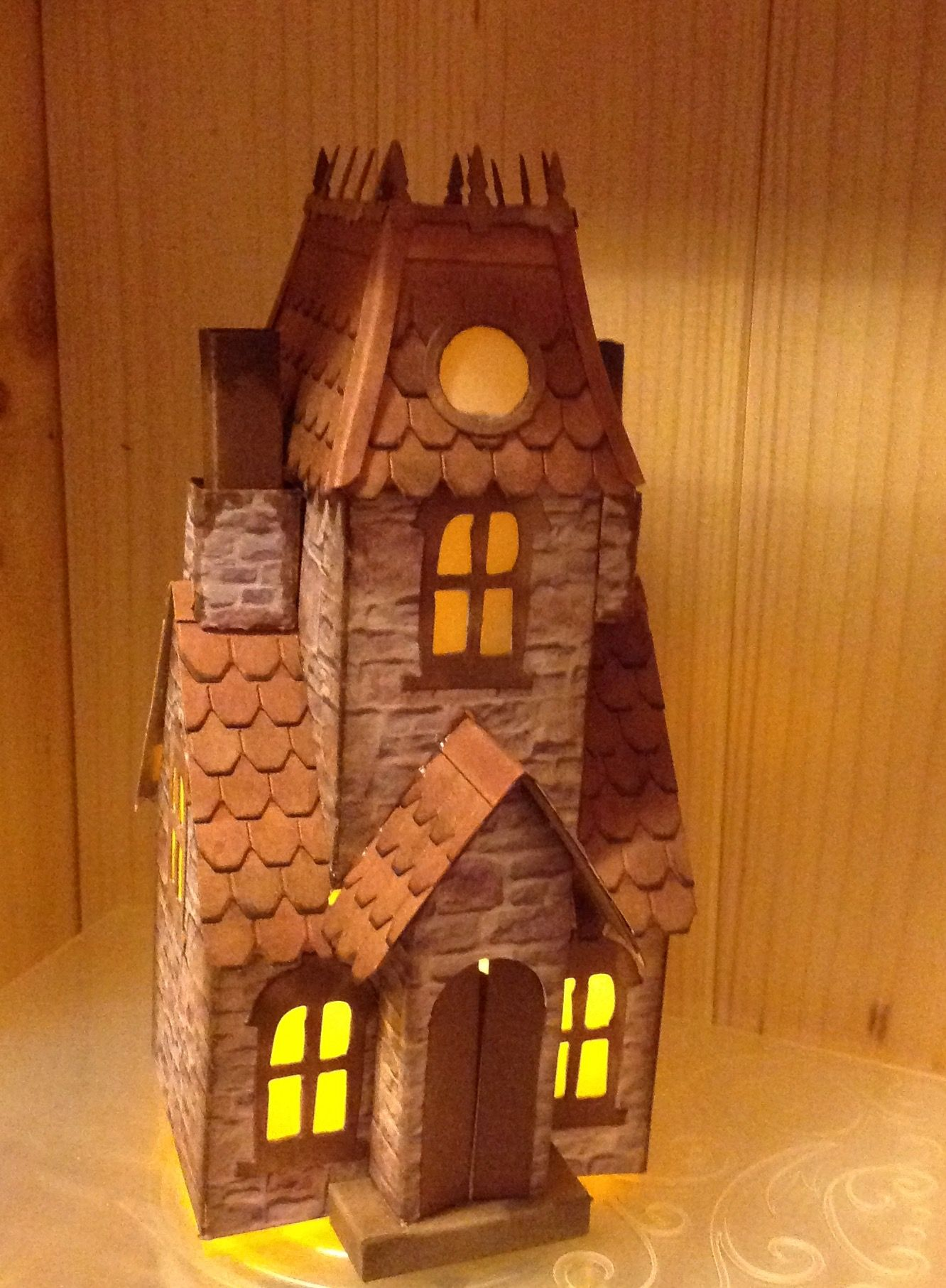 Tim Holtz Village  dwelling with Manor House addition. Stone paper for main walls. Roof with shingles. A slot cut in the main roof allows the light from the tea light to show at the upper Windows.
