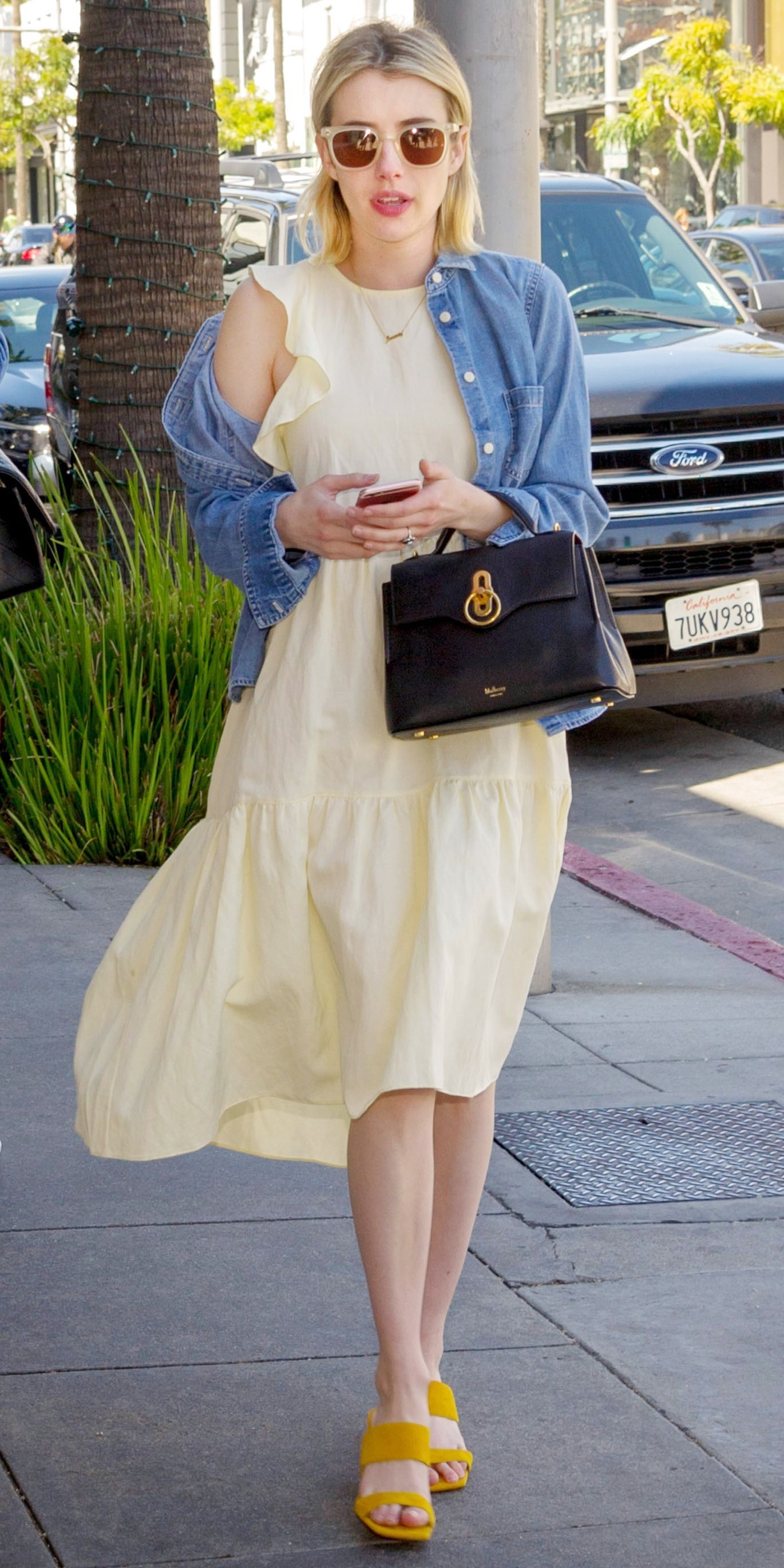 Emma Roberts Made Us Excited For Spring While Wearing A Pale Yellow Ulla Johnson Dress Denim Jacke Yellow Dress Casual Yellow Dress Spring Yellow Dress Outfit