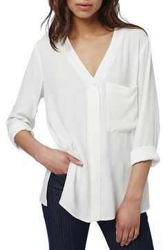 This loose and easy white blouse is styled with a single oversized chest pocket, side slits and split panels wrapping the breezy back.