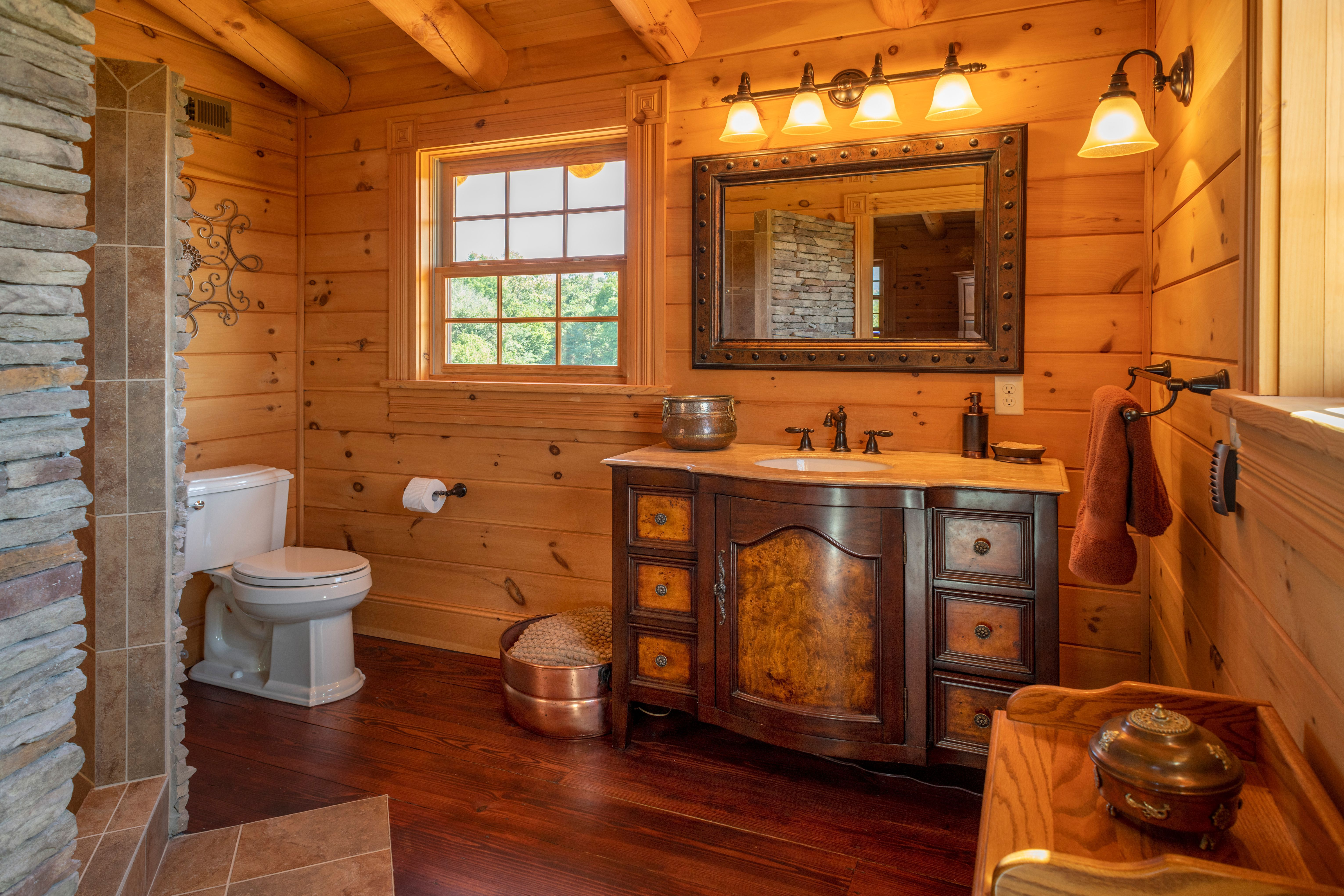 Stone and tile encase the walk in shower in this log cabin
